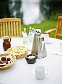 Laid table with Thermos jug and small cakes out of doors