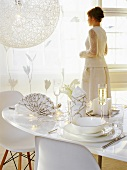 Woman dressed in white standing behind elegantly laid table