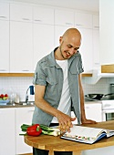 Man leafing through cookery book in kitchen