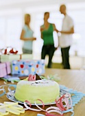 Marzipan-covered cake and gifts, three people in background