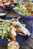 Barbecued fish, kebabs and salad