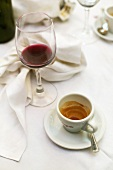 Empty espresso cup and red wine glass