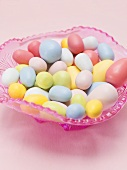 Coloured sugar eggs in pink glass dish