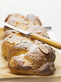 Bread plait with flaked almonds & icing sugar on baking parchment, knife