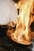 Chef flambéing a dish in a frying pan