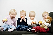 Four toddlers eating apples