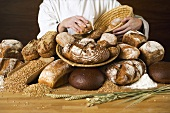 Baker with various types of bread and bread rolls