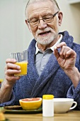 Elderly man taking tablet at breakfast