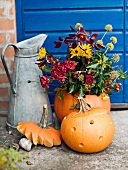 Metal jug, pumpkins and flower arrangement in front of house