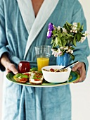 Man in dressing gown serving breakfast
