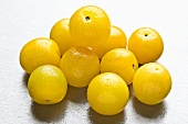 Several yellow plums with drops of water