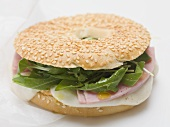 Ham, cheese and rocket in sesame bagel