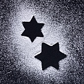 Star shapes in icing sugar on black background