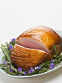 Glazed roast ham surrounded by herbs