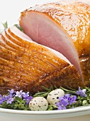 Glazed roast ham surrounded by herbs for Easter (close-up)