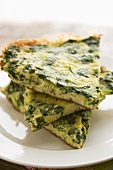 Slices of Chopped Spinach Frittata; Stacked on White Plate