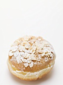 Doughnut with icing sugar and flaked almonds