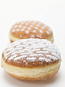 Two doughnuts dusted with icing sugar
