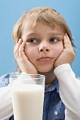Little boy sitting in front of glass of milk