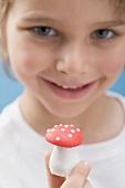 Little boy holding a marzipan mushroom