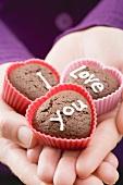 Hände halten Schokoladengebäck zum Valentinstag