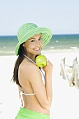Young woman in sun hat with green apple on beach