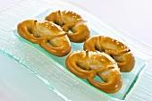 Four fresh soft pretzels on a glass plate