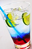 Coloured soft drink with ice cubes and lime slices