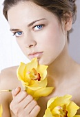 Young woman with yellow orchids