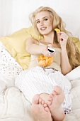 Blond woman with crisps and remote control lying in bed