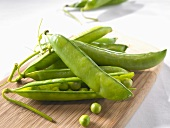 Pea pods and individual peas on chopping board