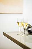 Two glasses of white wine beside pile of plates on table corner