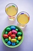 Chocolate eggs in coloured foil and two glasses of juice
