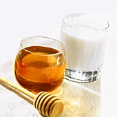 Glass of honey, honey dipper and glass of milk