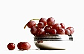 Fresh red grapes in and beside silver bowl