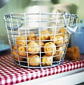 Potatoes in wire basket on kitchen table