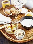 Muesli ingredients, eggs, bread, jam on breakfast tray