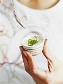Woman holding small dish of panna cotta with lime zest