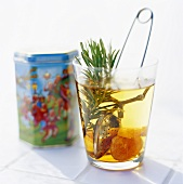 Tea with rosemary and dried fruit in glass, tea tin