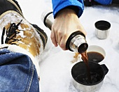 Hand pouring hot coffee from Thermos flask into cup