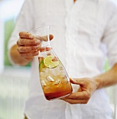 Mann hält Karaffe mit fruchtigem Getränk