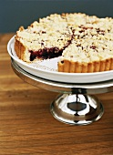 Berry crumble tart on cake stand
