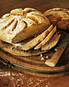 Crusty bread, partly sliced, on breadboard