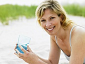 Woman with glass of water on beach