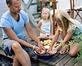 Father and daughters peeling potatoes out of doors