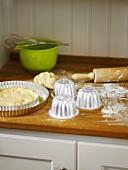 Dough, baking tins and baking utensils in kitchen