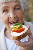 Woman eating bread with cream cheese, tomato and basil