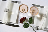 Two place settings for a celebration with champagne glasses and a red rose