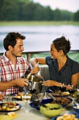 Couple eating barbecued food out of doors by a lake