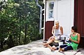 Zwei Frauen waschen Geschirr vor einem Holzhaus (Schweden)